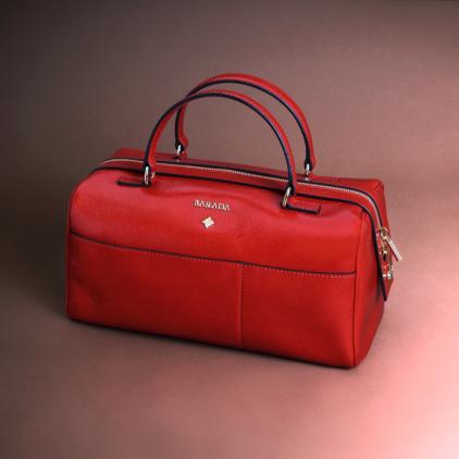 Bolso de napa roja acharolada con forma redondeada en bordes, muy actual
